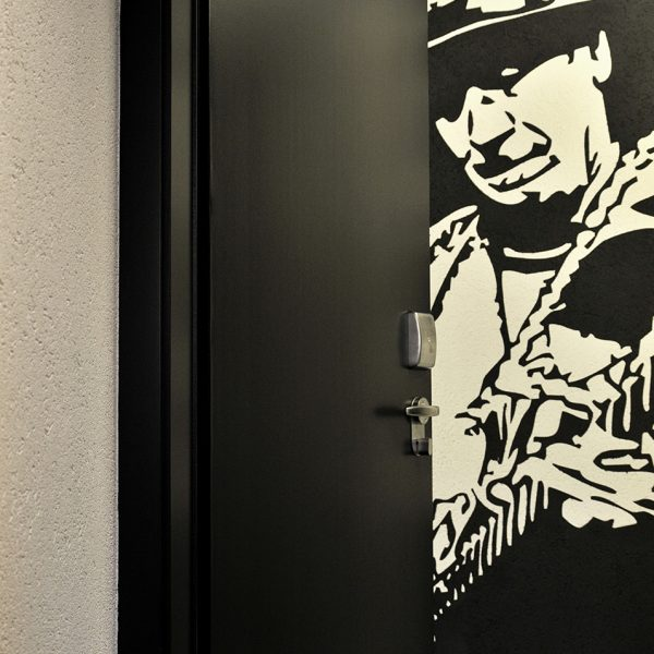"Open door to one of the Tralala Hotel Montreux ""S"" Small Rooms revealing artwork of Carlos Santana"