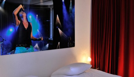 """Montreux Jazz festival print above bed in """"L' Large Rooms accommodation at Tralala Hotel Montreux"""
