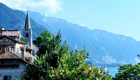 A classic Montreux Swiss Riviera scene with a church spire & mountains beside Lake Geneva