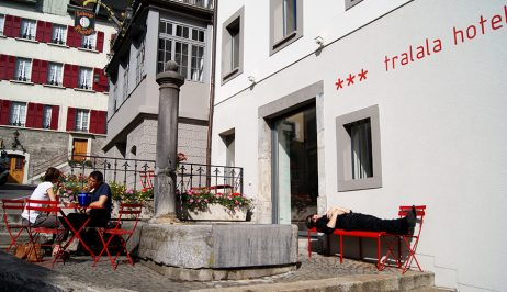 Visitors relax on chairs & bench outside Tralala Swiss Design & Lifestyle Hotel in historic Montreux